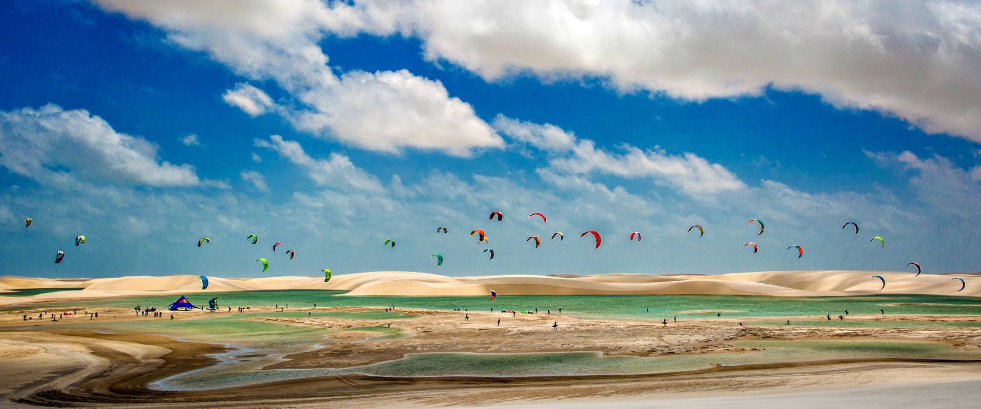 A group of people kitesurfing among the sand dunes of Lençóis Maranhenses