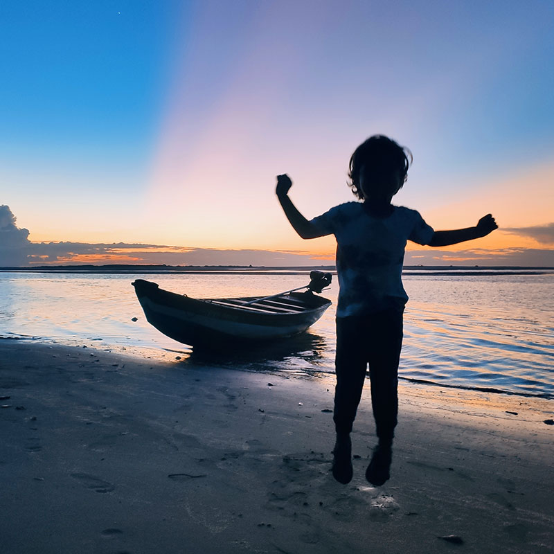 A kid enjoying the sunset on a beach next to a boat in Atins