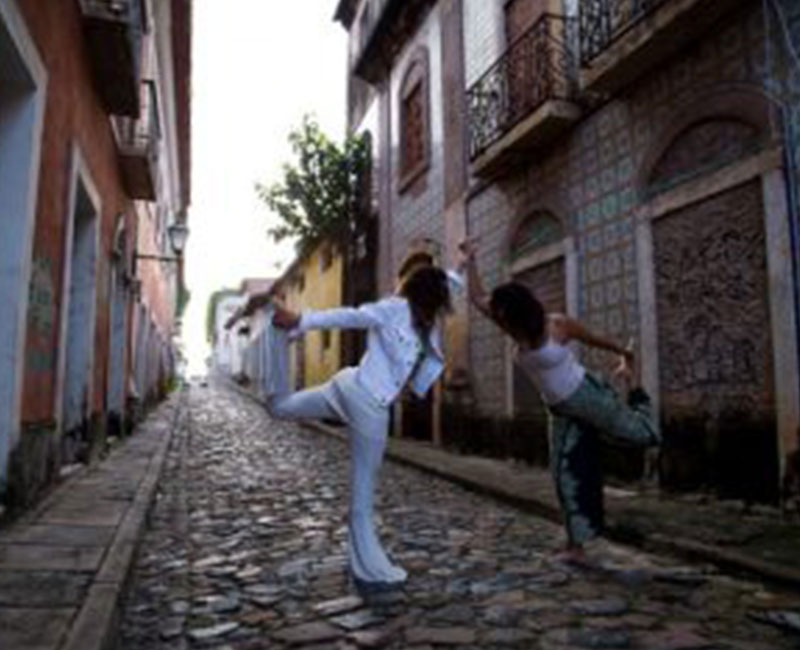 A couple posing with a yoga pose on a cobble stoned street