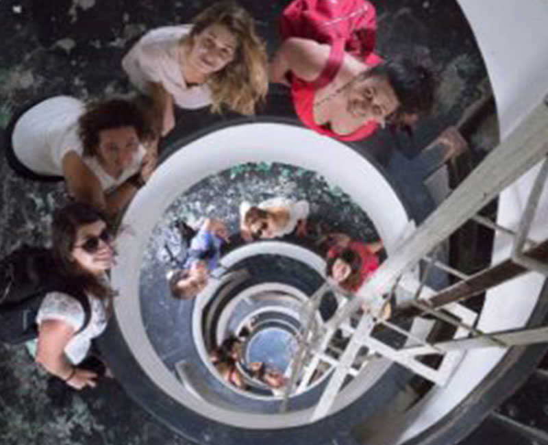 A group of people posing for a photo looking up in a circular staircase