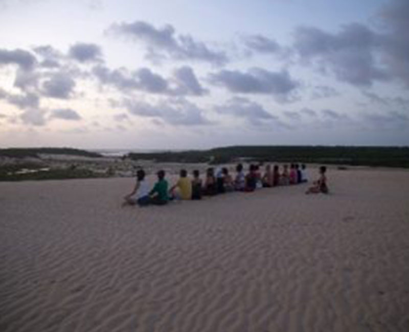 A group of people meditating on the sand dunes in Atins, Brazil