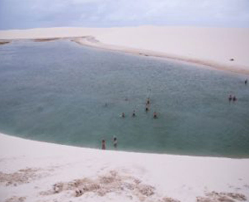 A group of people taking a dip in a lake on the sand dunes of Atins