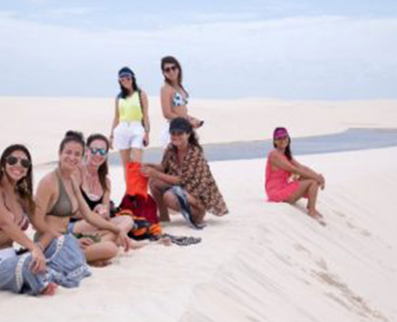 a group of people sitting on the sand dunes of Atins, Brazil
