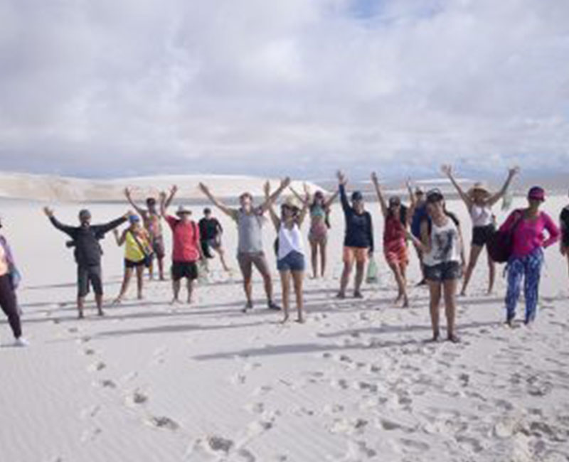 A group of people posing for a picture on the sand dunes of Atins