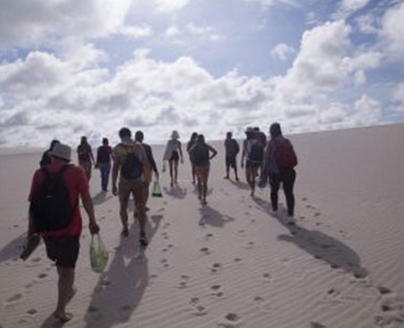 Group of people walking along the sand dunes of Atins, Brazil