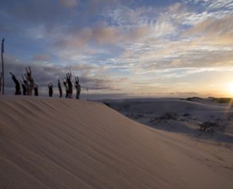 A group of people doing yoga at sunrise on the sand dunes of Atins