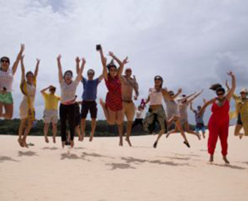 A group of people jumping up on the sand dunes of Atins