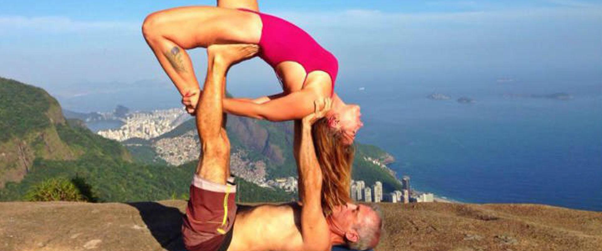 A couple doing a creative yoga pose on top of a mountain