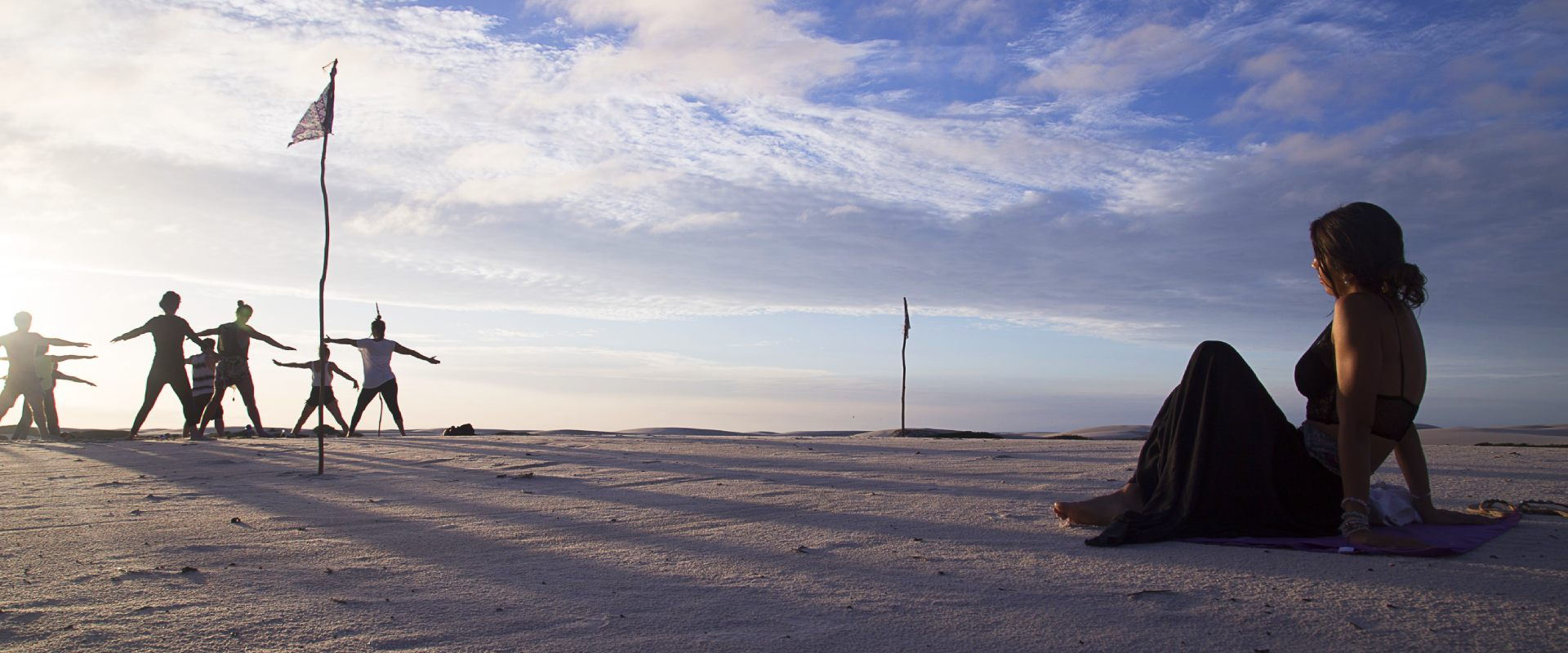 A girl looking at a group of people doing yoga on the sand dunes in Atins