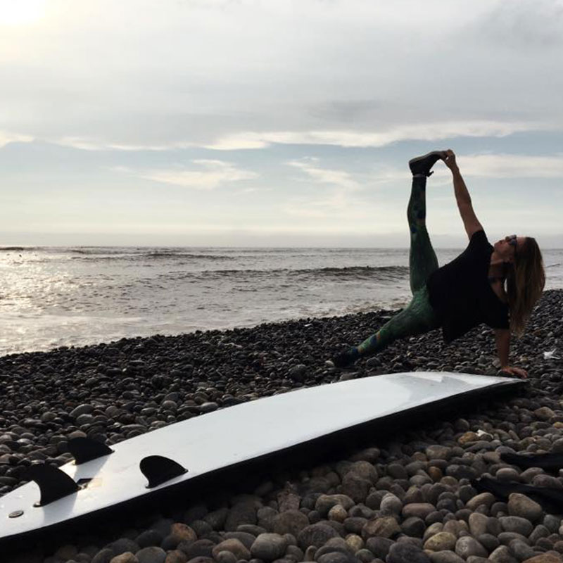 A person doing a yoga pose on the beach behind a surf board